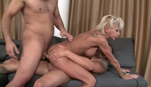 A hot milf is getting ass drilled during the time that she is giving a blow job. She loves to have sex in a threesome since then all her holes get filled up at once.