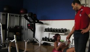 Trainer helps a babe work out on the equipment previous to he nails her