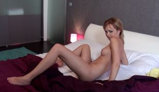 A redhead that loves to show off is on the bed, nude, jacking off