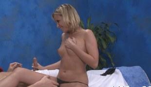 Slender blonde goddess riding her massage client on a table